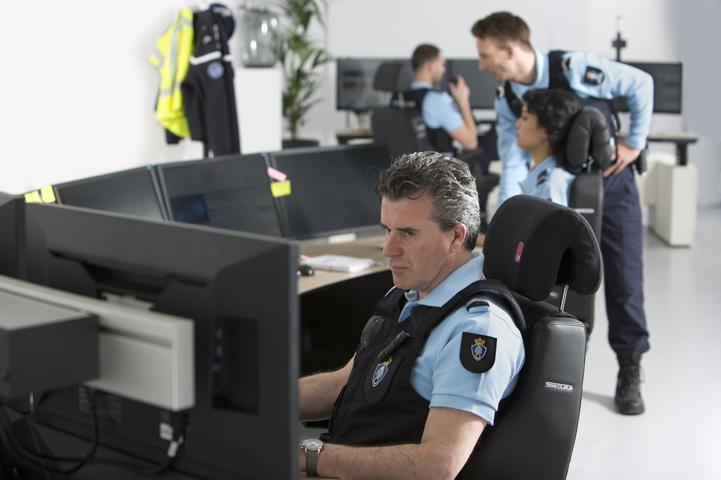 Security guard sitting on Black leather Secur 24 desk chair looking at surveilance monitors with other security guards in the background