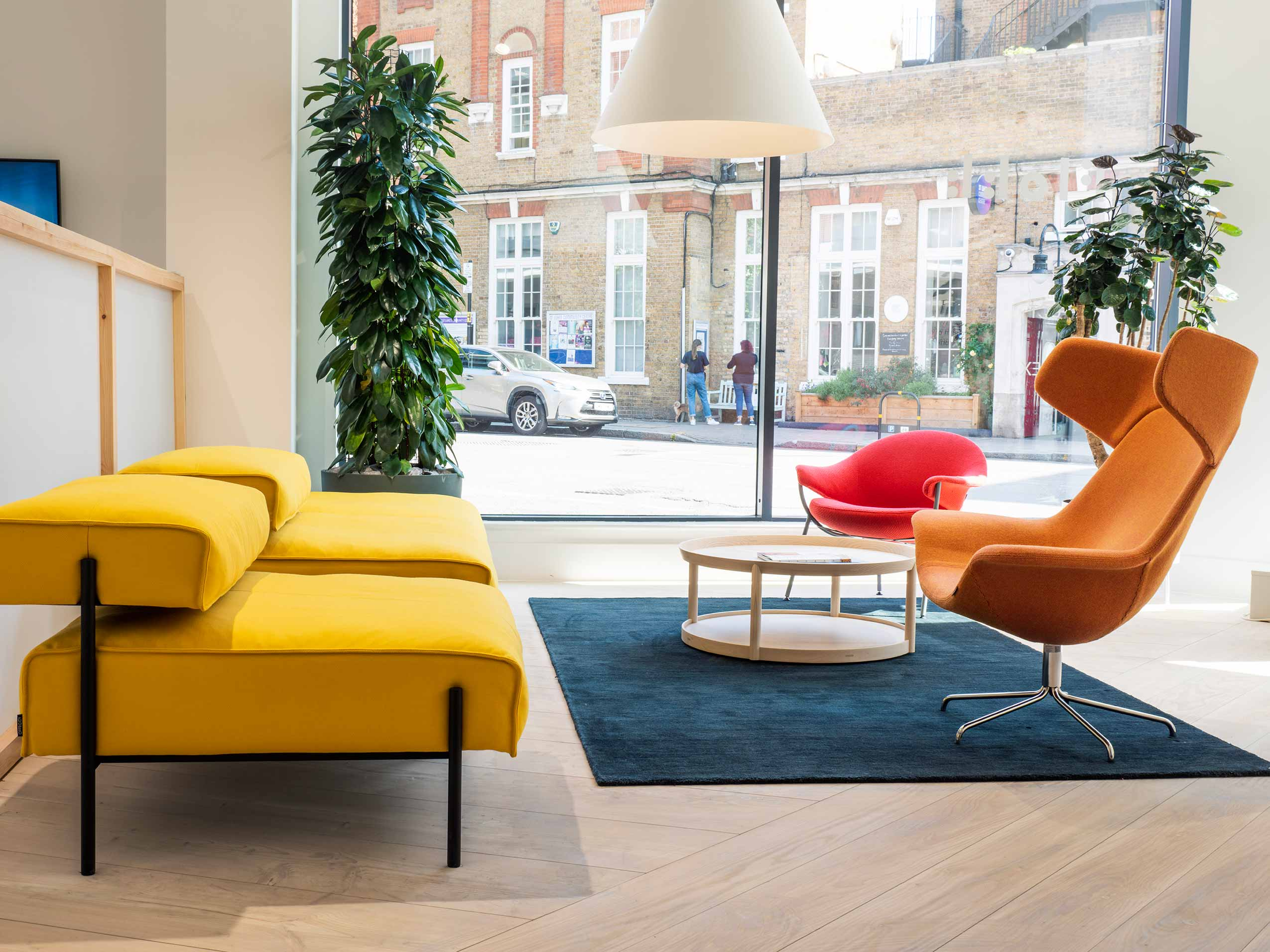 UK Flokk showroom featuring OFfecct yellow sofa, red and orange chairs