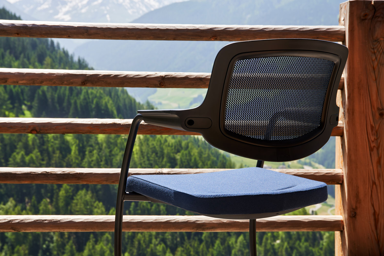 close up of blue giroflex 161 visitor chair with a wooden railing behind it, with mountain forests in the background