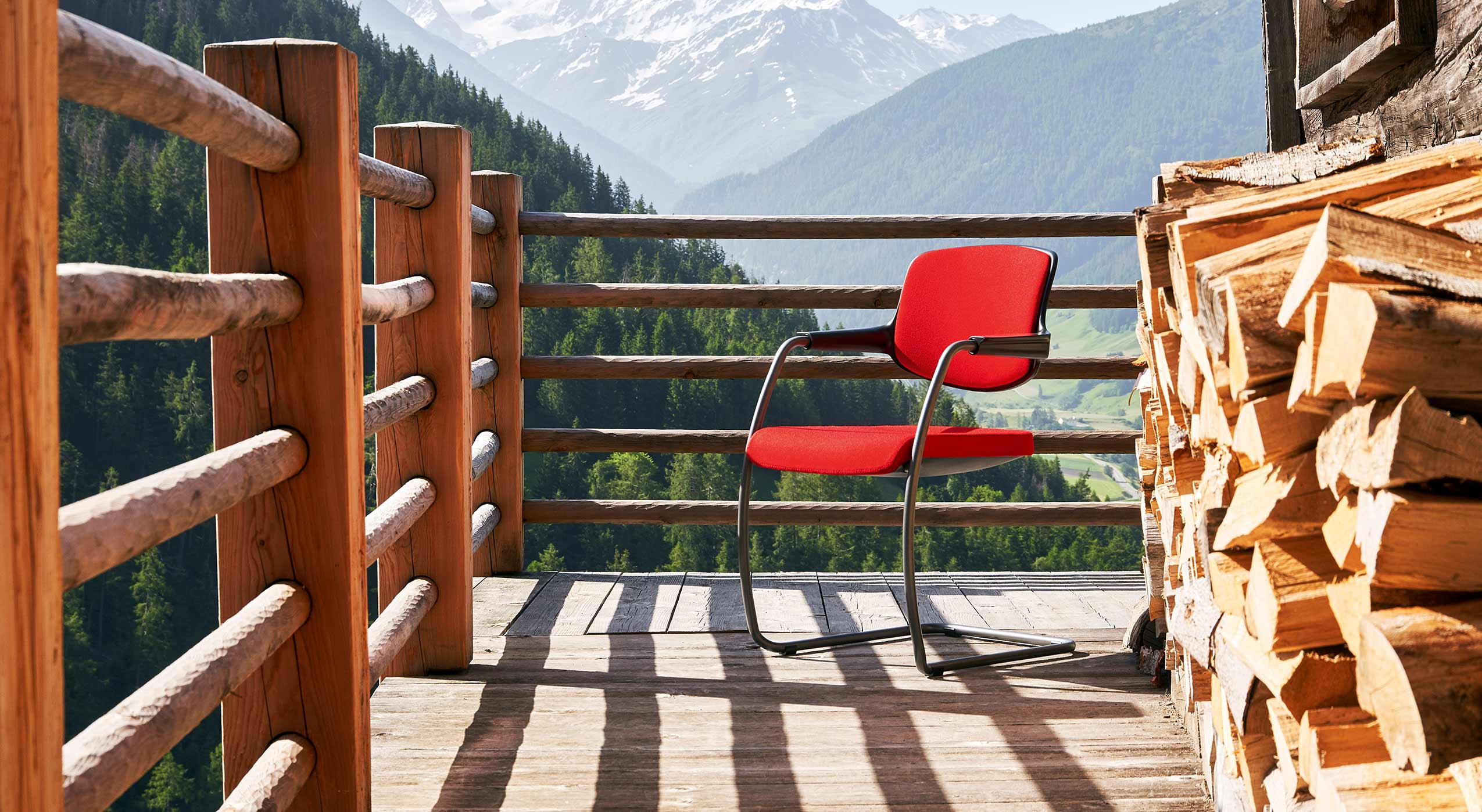Red giroflex 161 visitor chair on a wooden balcony in the Swiss mountains