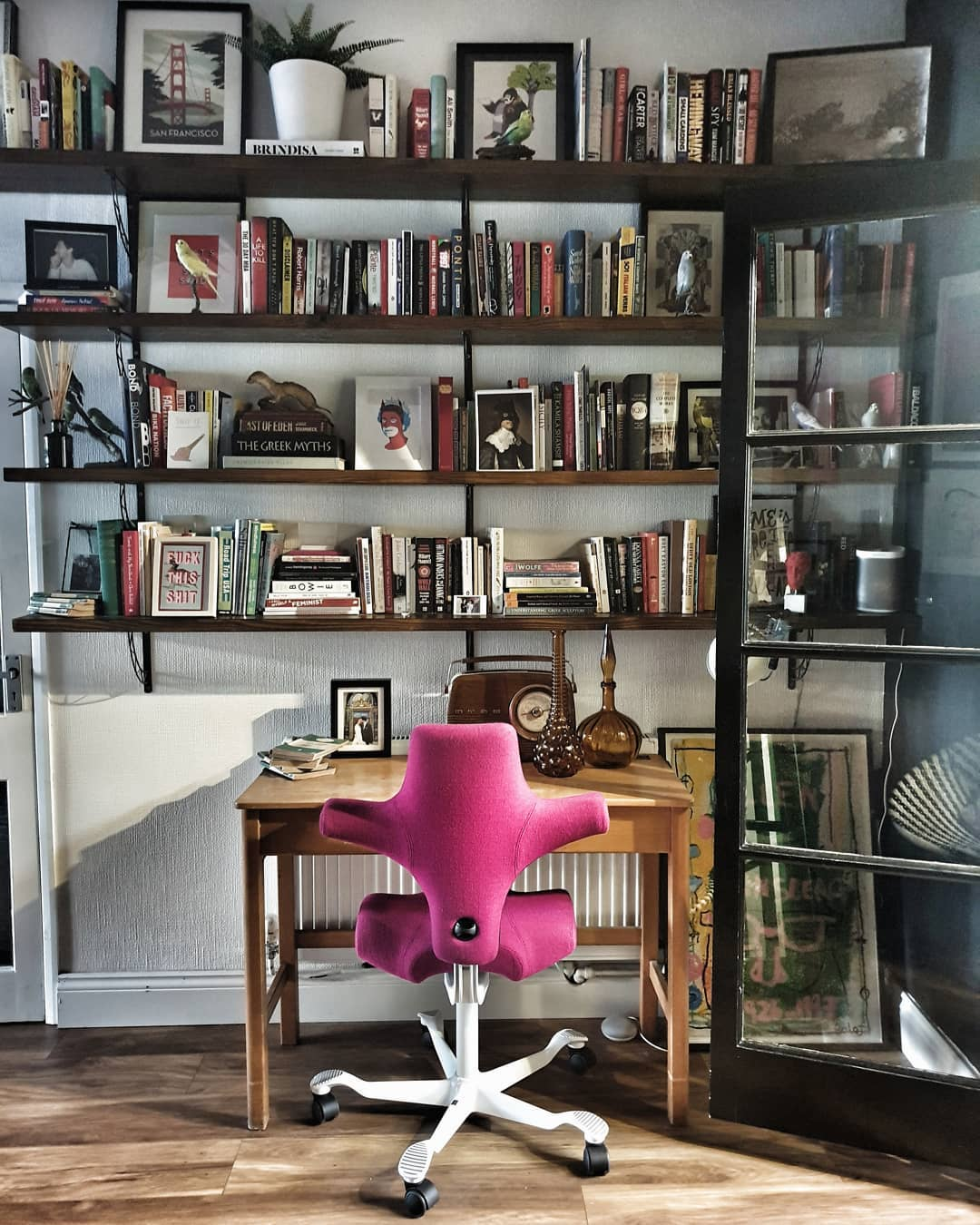 rustic home office featuring HÅG Capisco in pink fabric with large bookcase and old fashioned desk for working from home