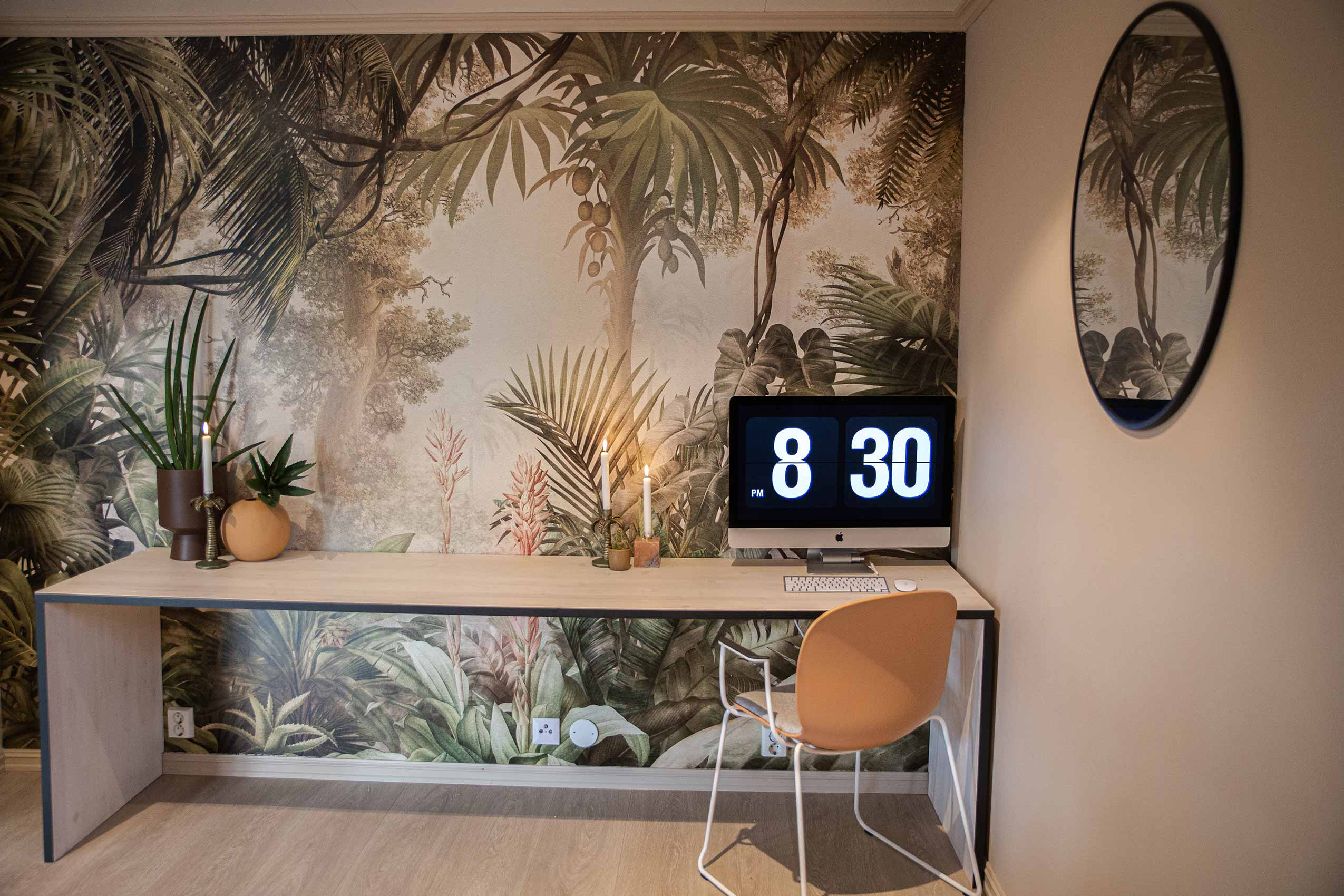Coral RBM Noor chair at a side table with a palm treee mural wall covering and a clock showing 8:30