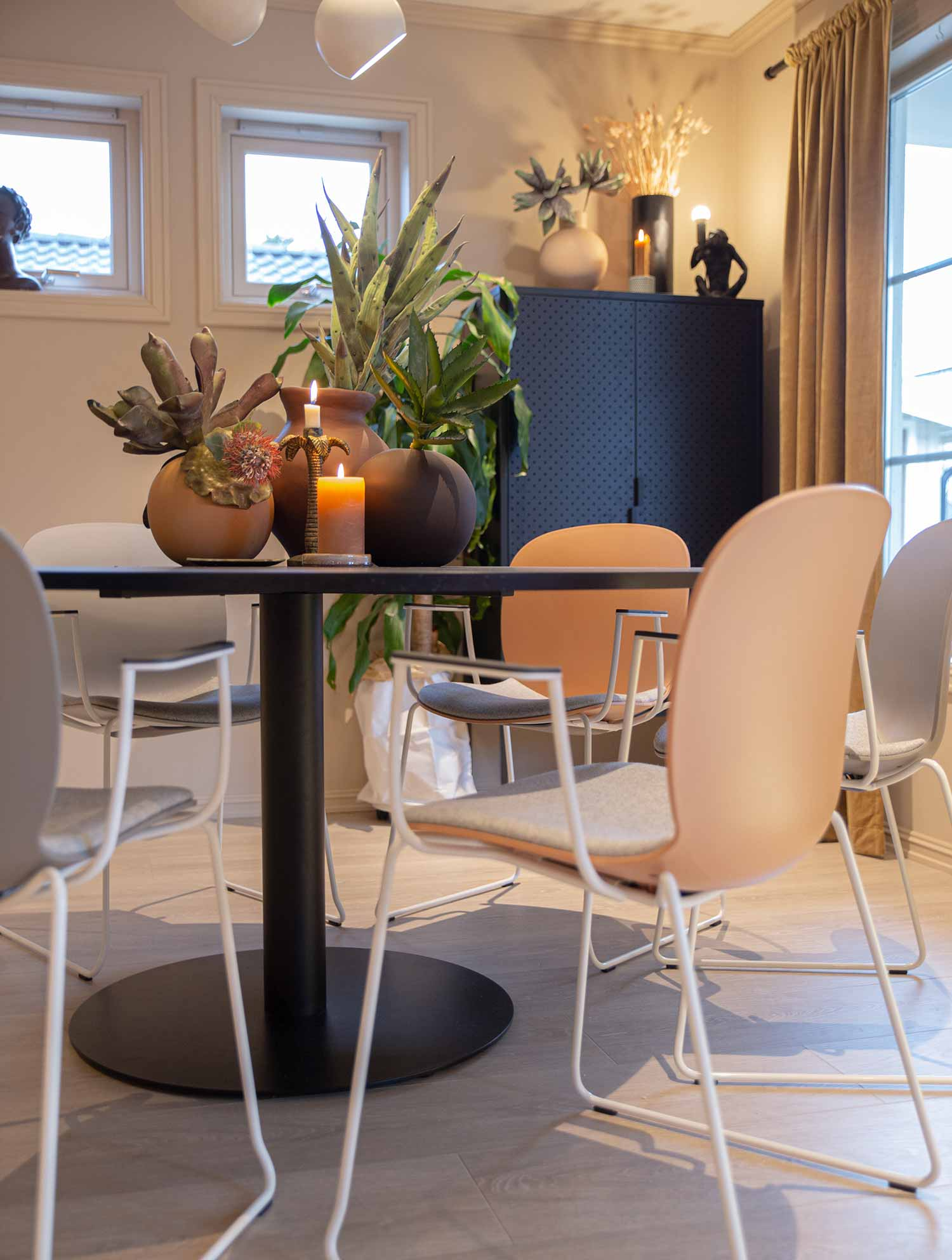 Close up of coral RBM Noor chair in a home dining room with peach walls and a round black table