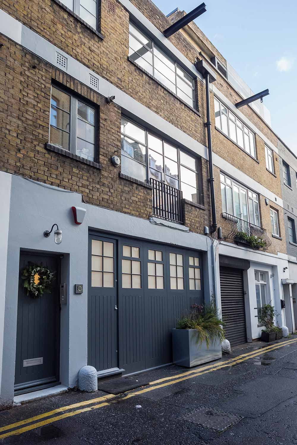 exterior of brick building housing Ruth tomlinsons atelier in London with blue door