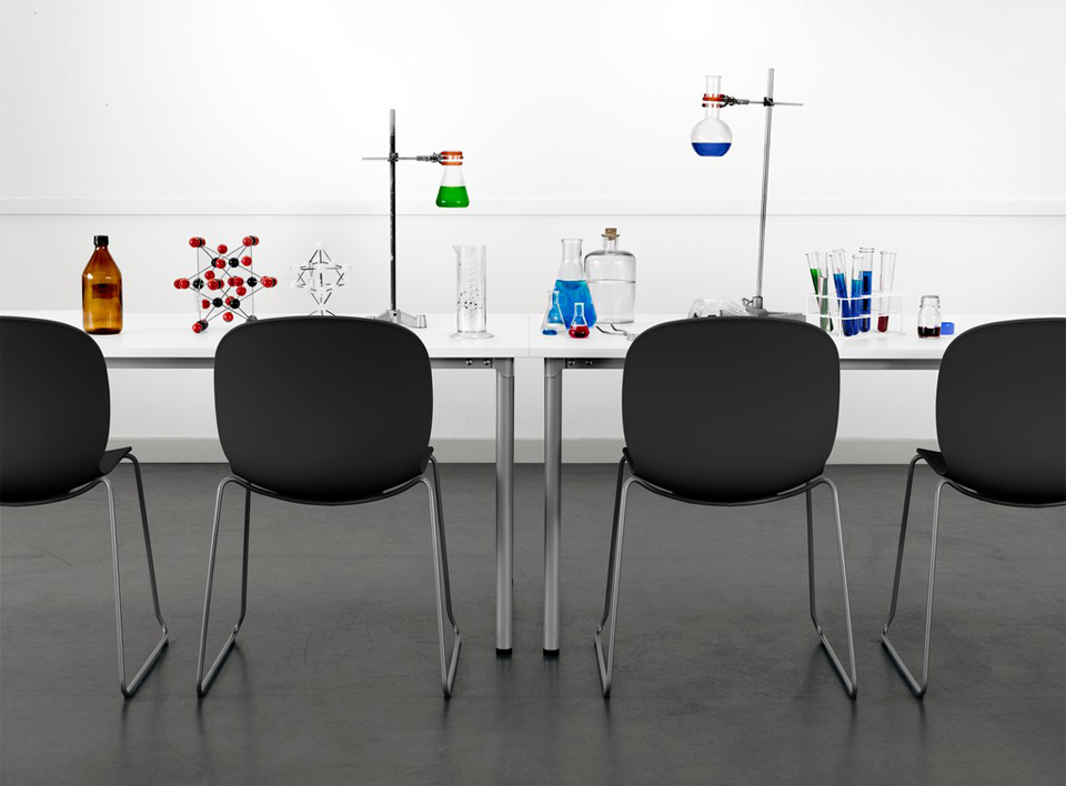Black RBM Noor chairs and RBM Eminent tables in the chemistry room with science experiments on the tables