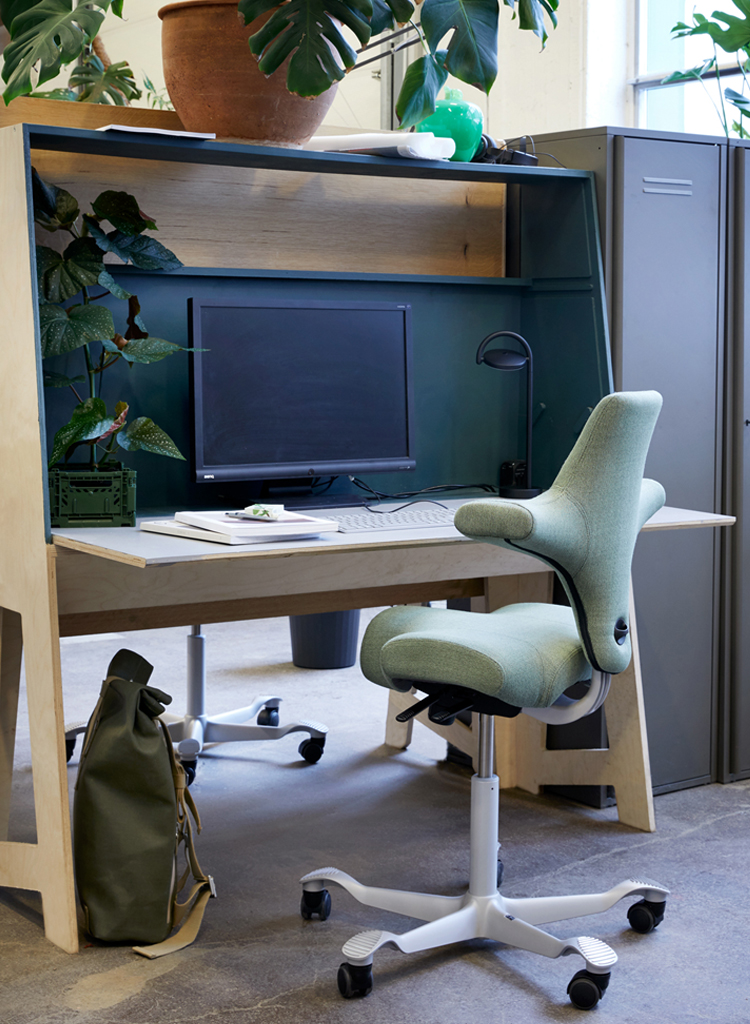 HÅG Capisco ergonomic chair in green fabric at a tidy workstation with computer and bag