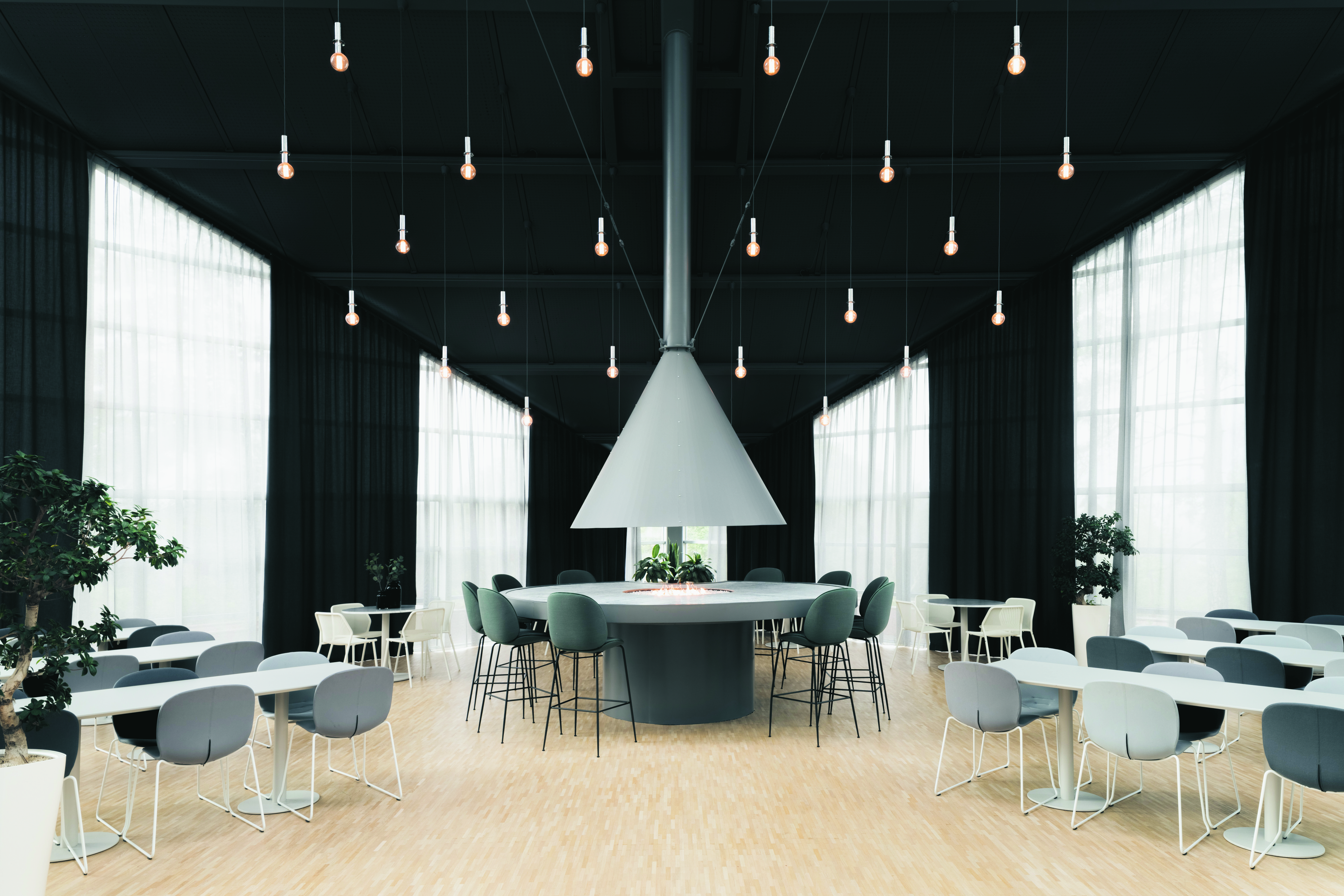 open canteen environment with dark walls and ceiling and hanging lights, with grey RBM noor chairs at tables
