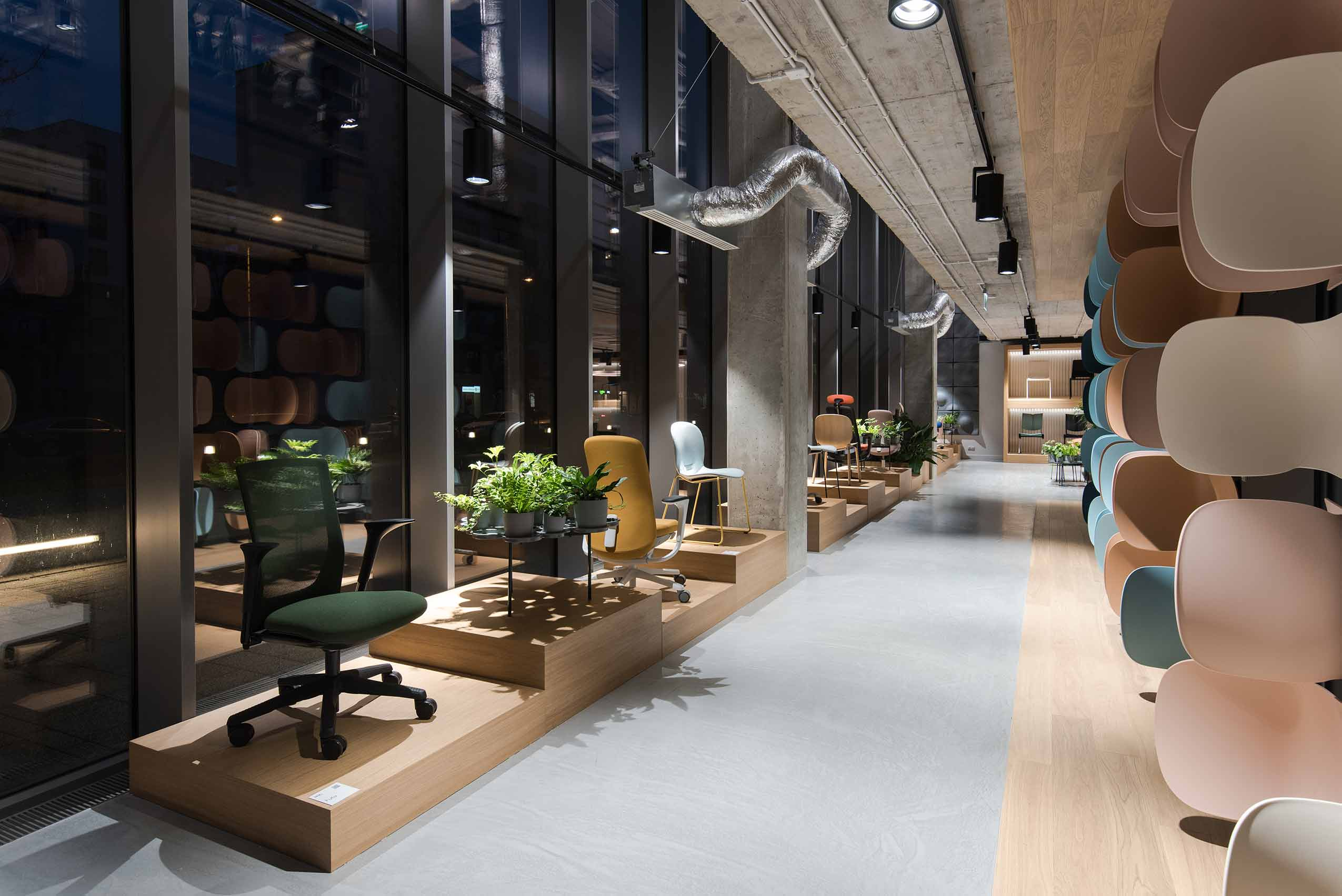 Flokk showroom in Poland with chairs on plinths in low light