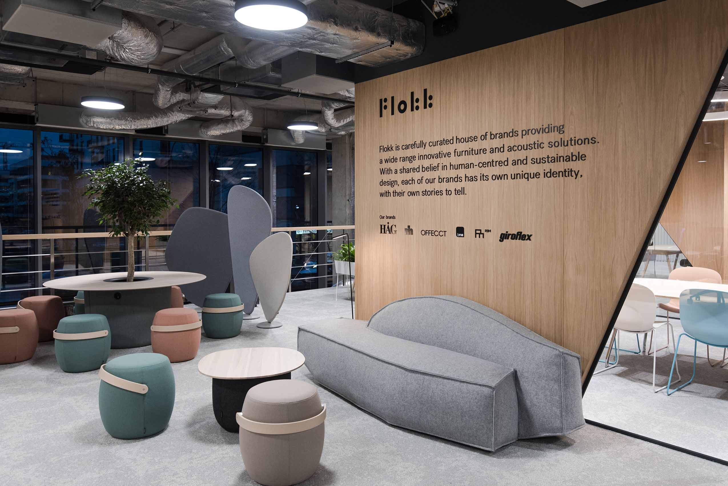 Flokk showroom in Warsaw poland, with a range of offecct carry on stools sat around tables and a sofa