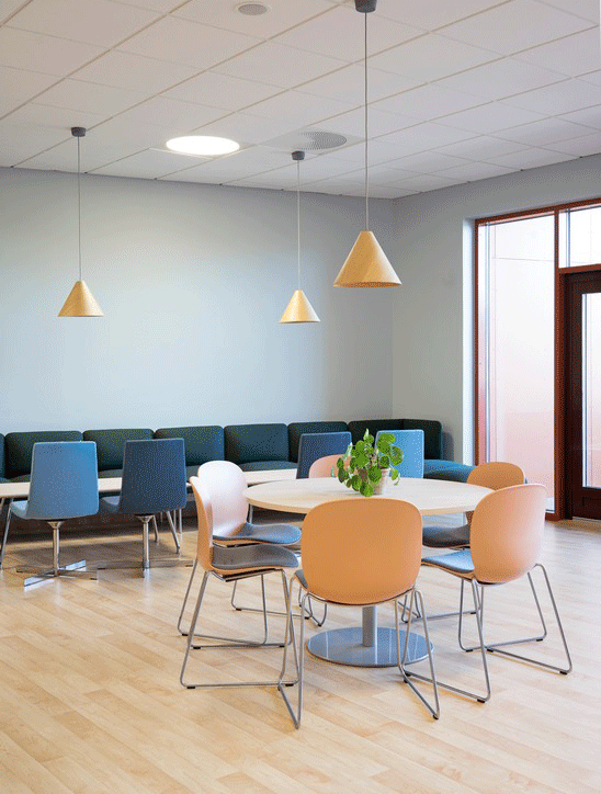 Clay coloured RBM Noor chairs arranged around a round table with pendant lighting in a cafe at Hebekk School, Norway