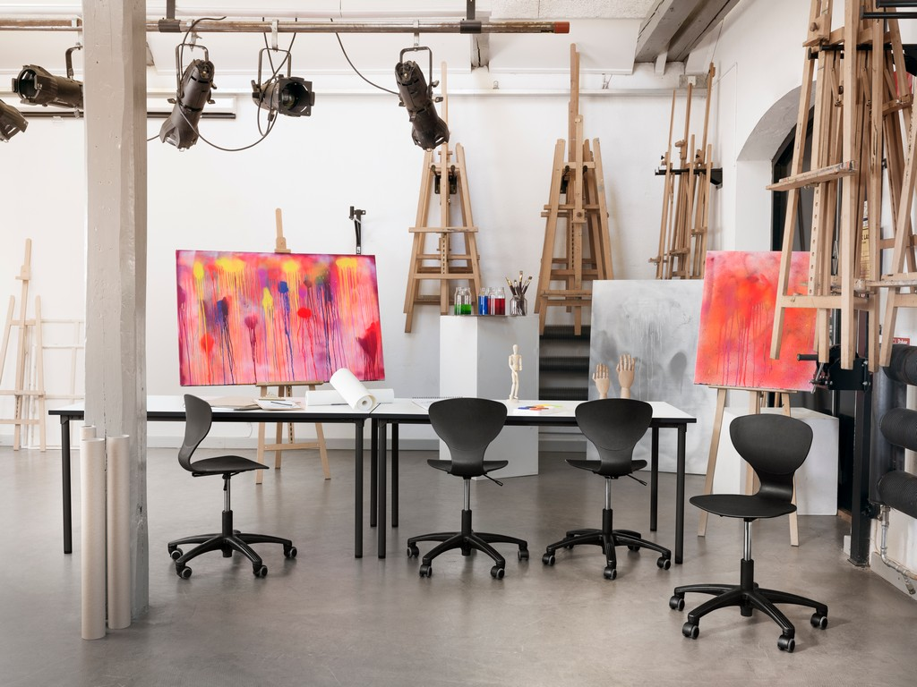 4 black RBM Ballet chairs in an art classroom with red abstract painting on aisles
