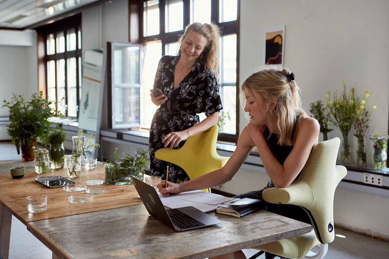 two ladies doing deskwork whilst sat on HÅG Capisco chairs