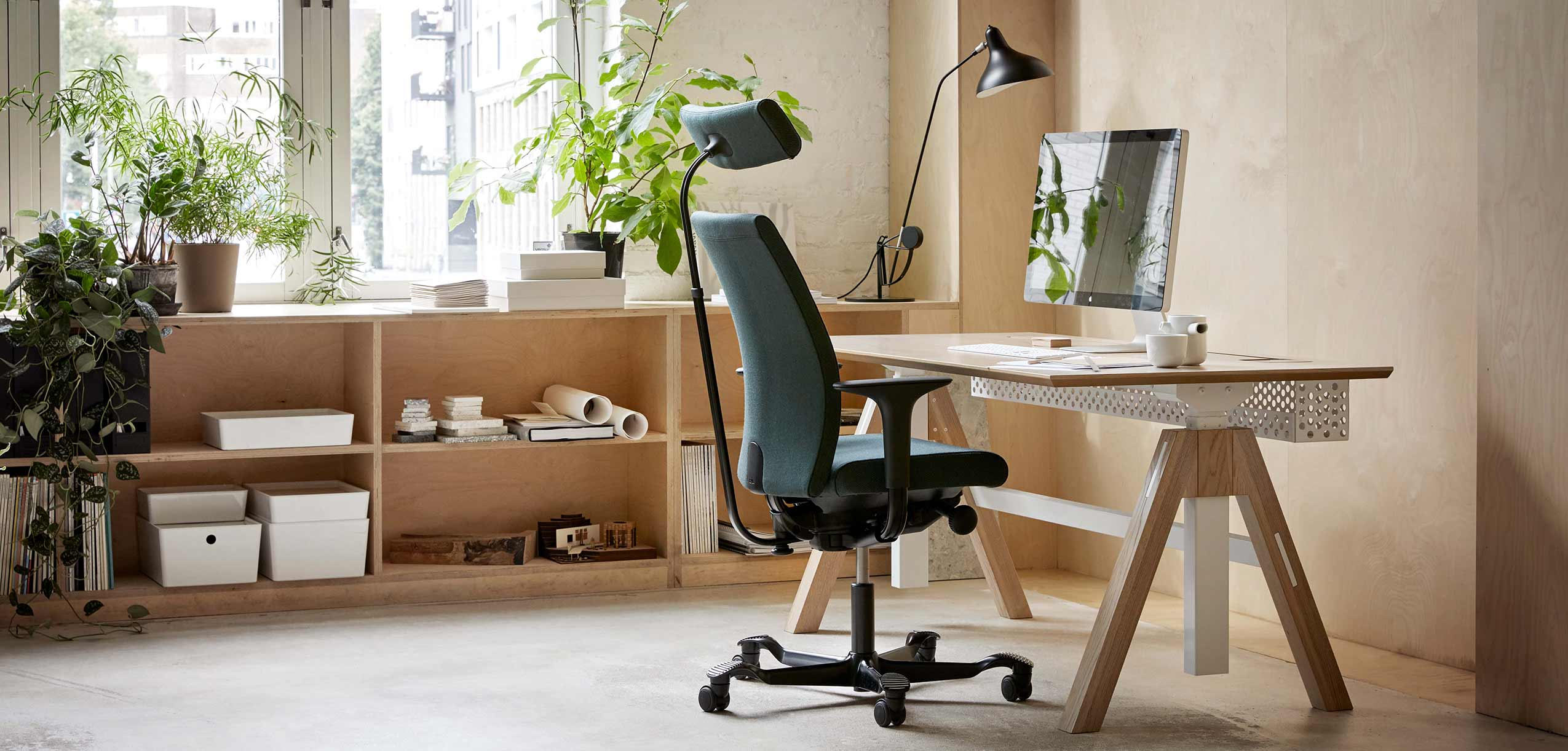 dark green HÅG Creed chair at a wooden height adjustable desk with an apple mac on it in a light office