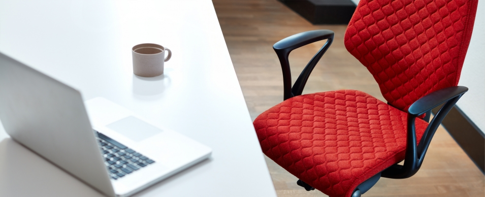Red quilt fabric on giroflex 64 chair at a desk with a laptop