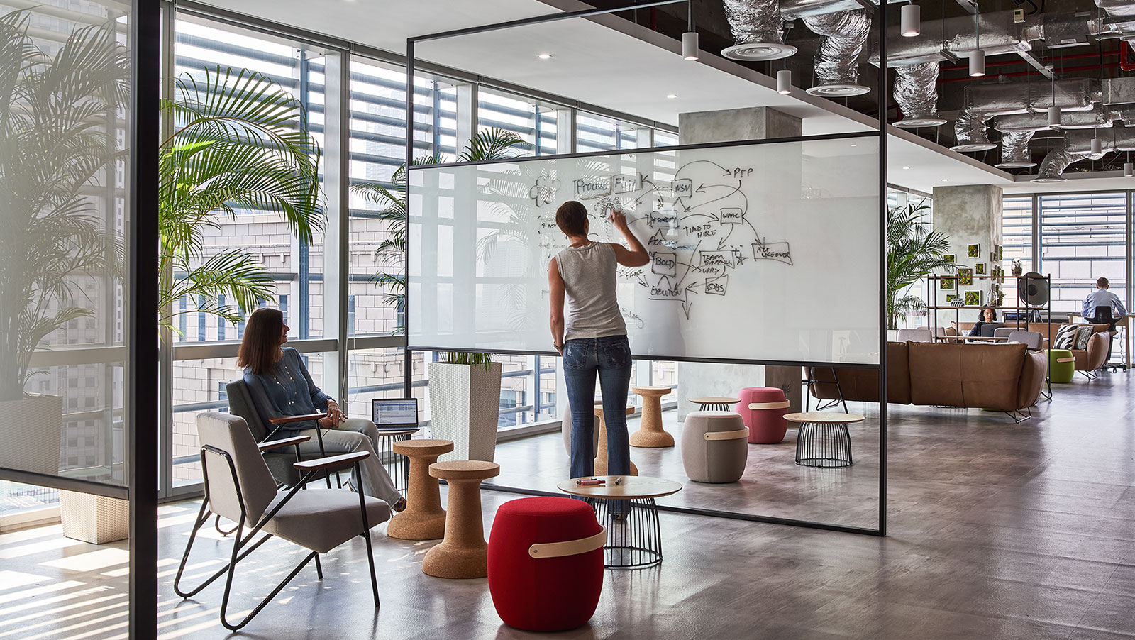 two people brainstorming on a whiteboard in modern office featuring Offecct carry on chairs