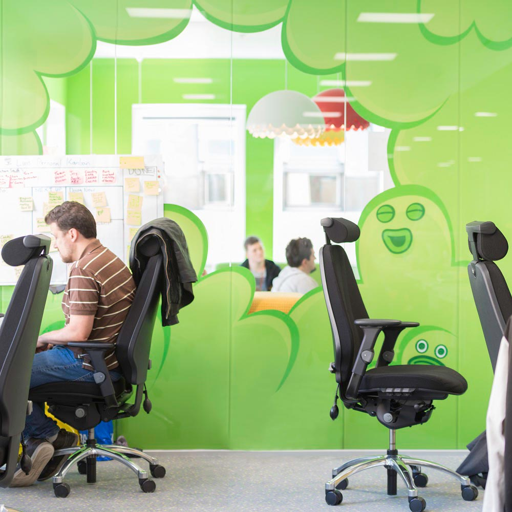 green artwork on the wall at King offices, with RH Logic chairs