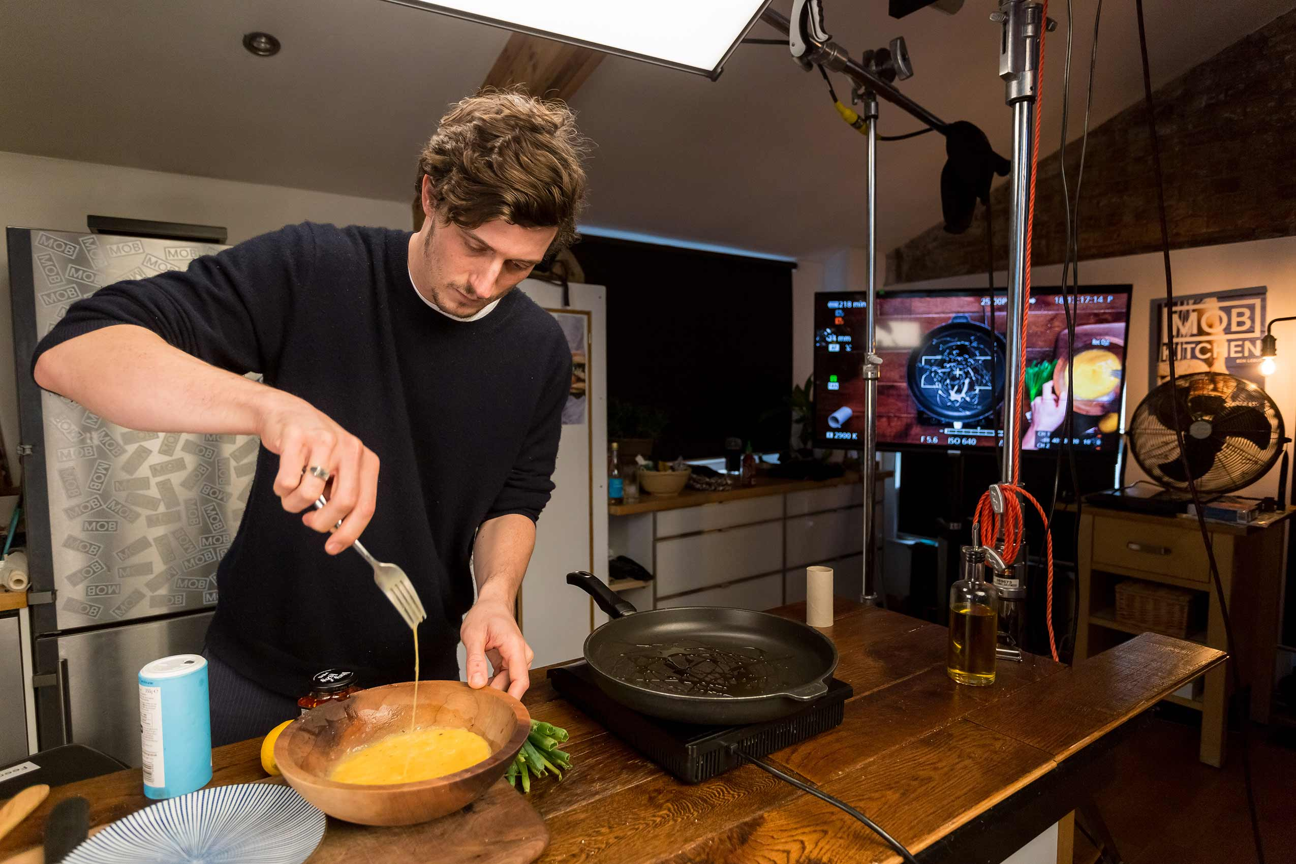Mob Kitchen founder Ben Lebus scrambling eggs with a fork in a wooden bowl in his office kitchen