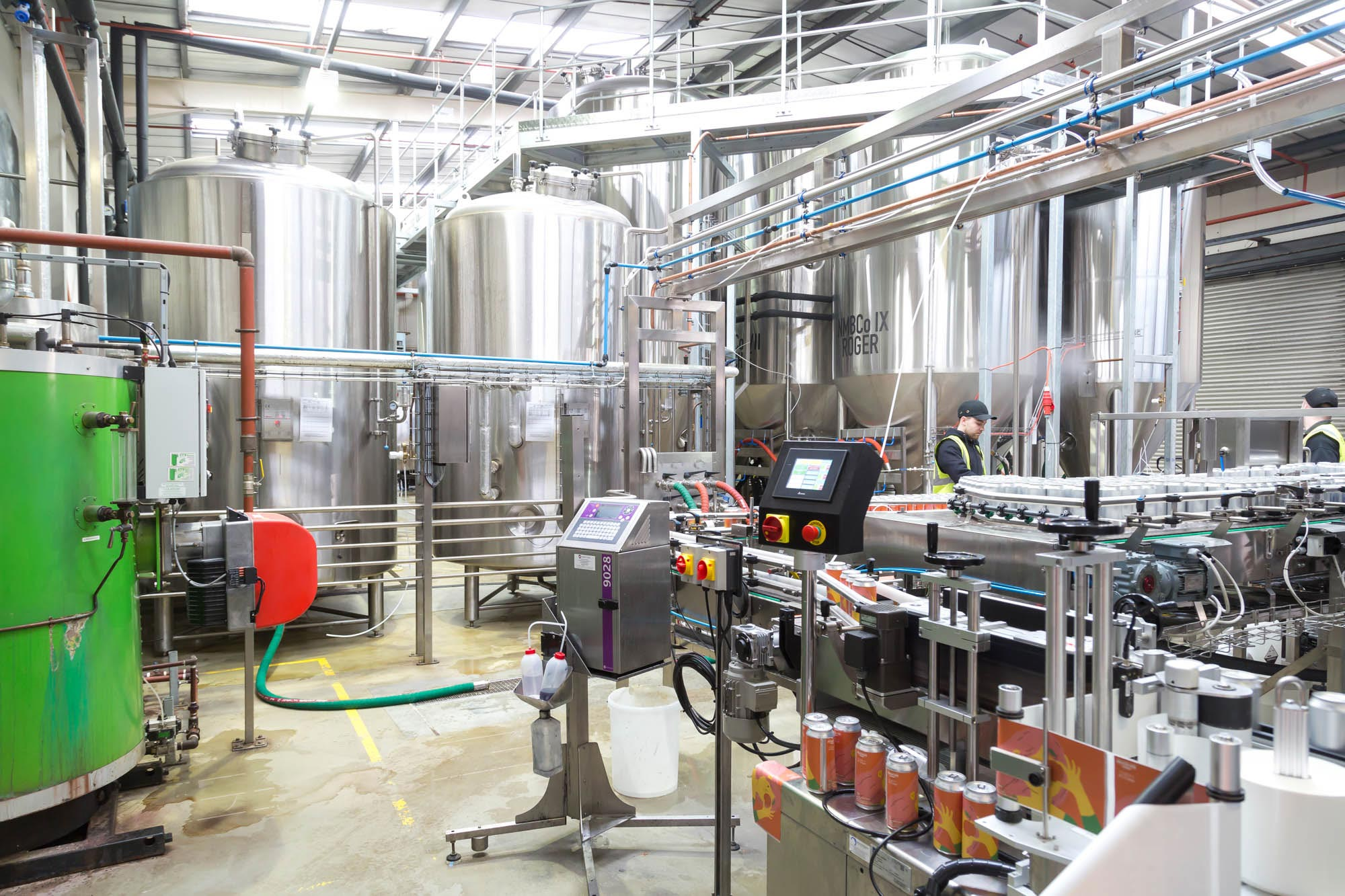 interior image of Northern Monk brewery with various brewery equipment including a canning machine