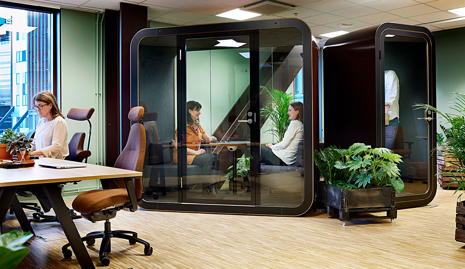 2 people inside a glass meeting booth in coworking office pop in work in sweden