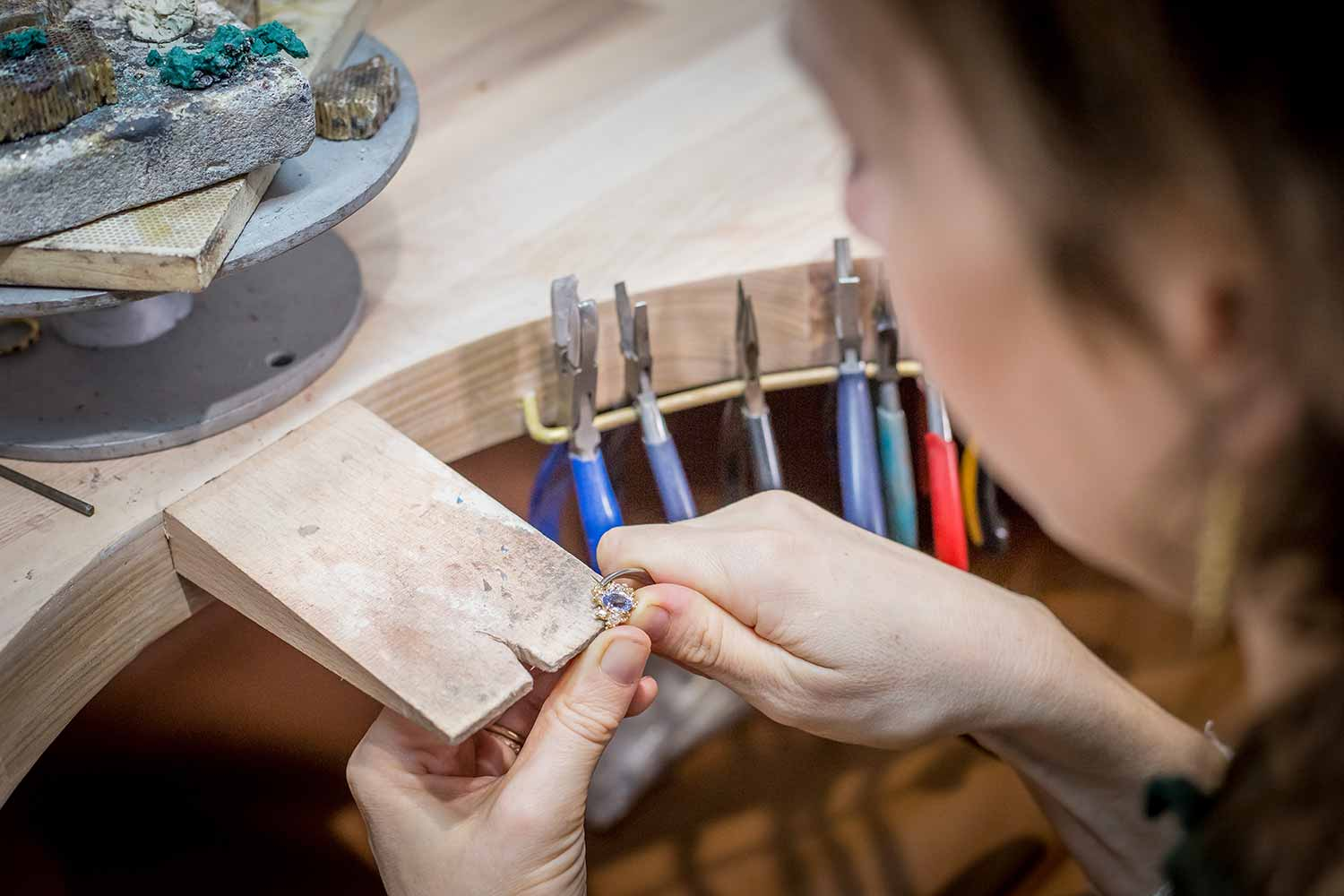 close up of jeweller Ruth Tomlinson working on a piece of jewellery with her hands on a wooden clamp