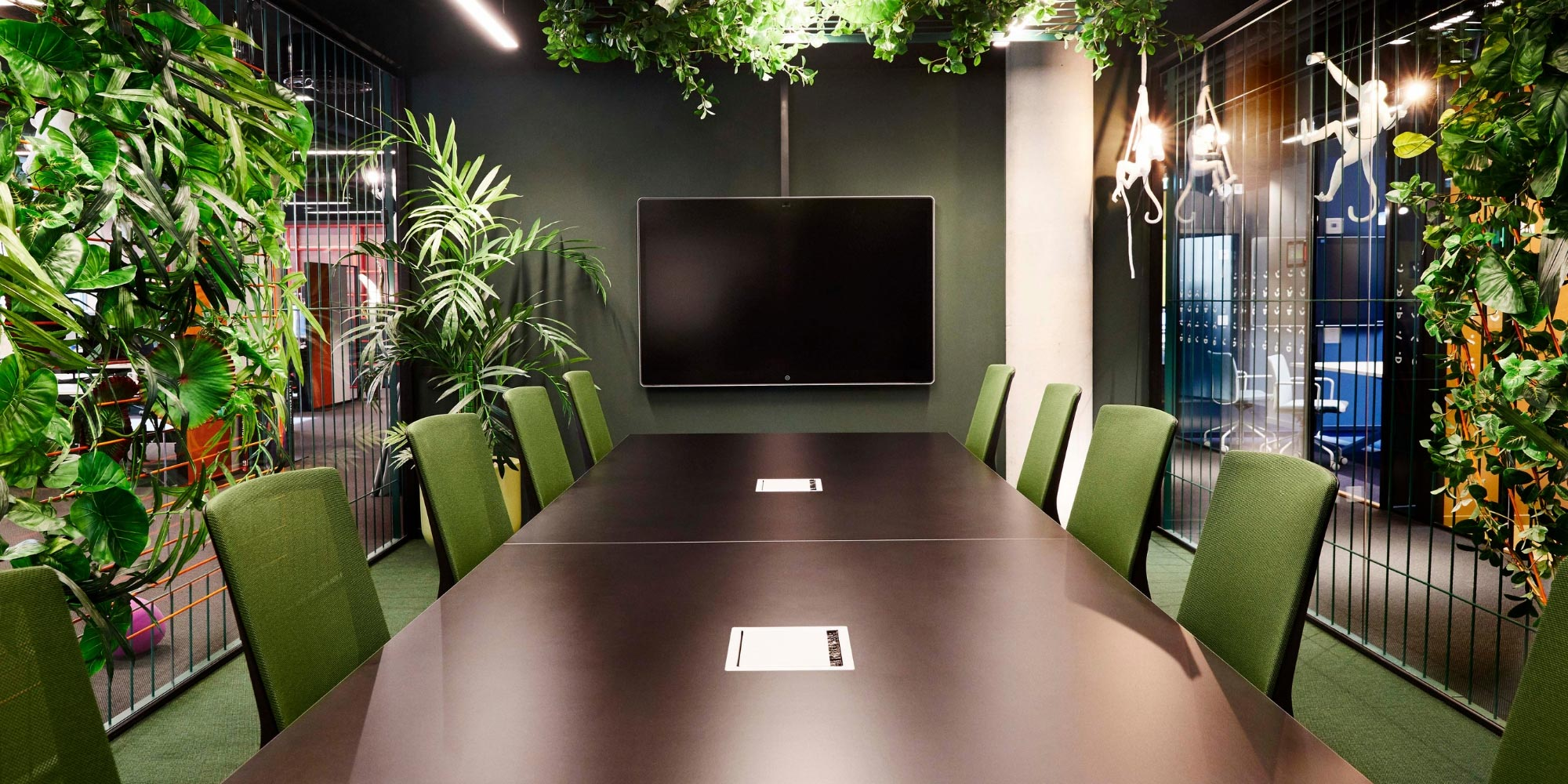 green meeting room with HÅG Futu chairs round a table and plants on the walls