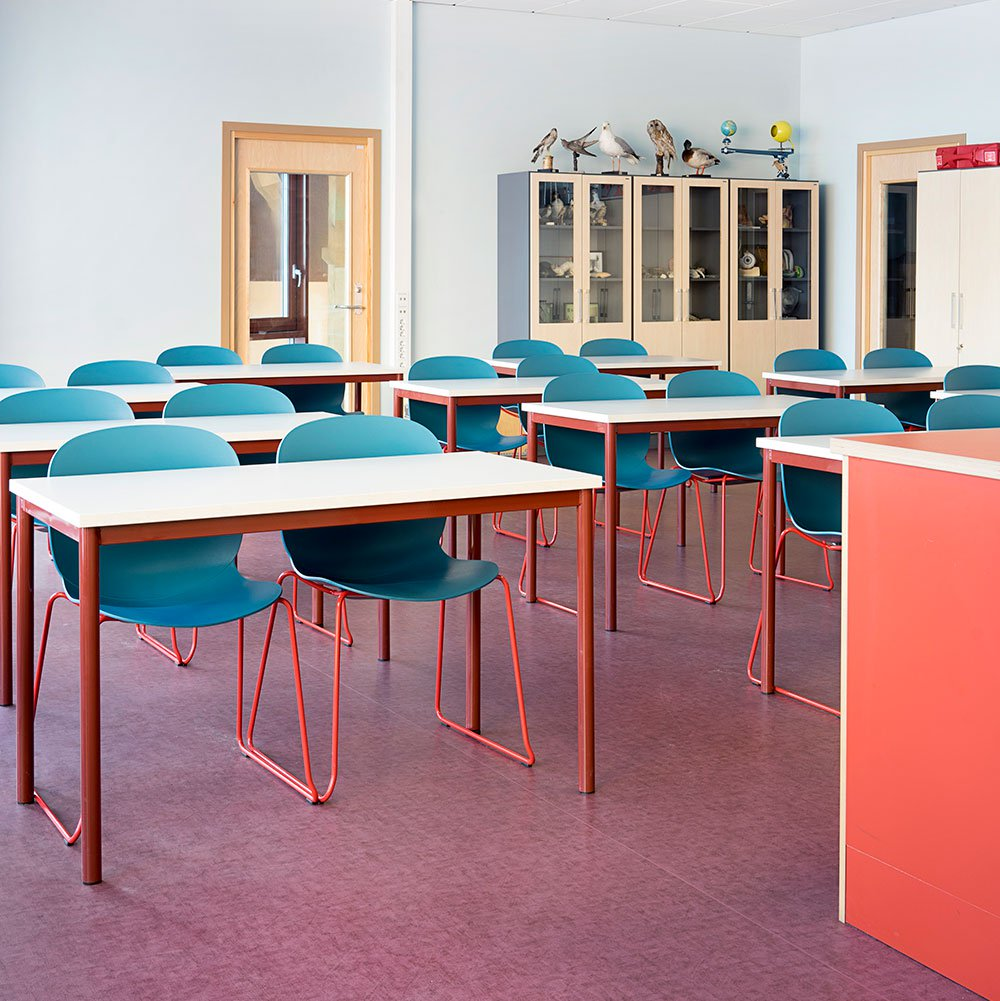 classroom with rows of blue RBM Noor chairs with red sledgebase legs at Hebekk School, Norway